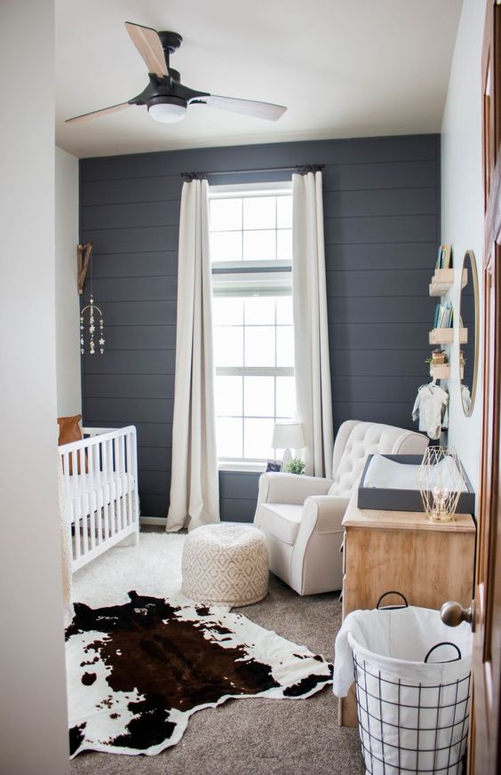 a farmhouse nursery done with a cute mobile, a printed ottoman and a faux animal skin as boho touches