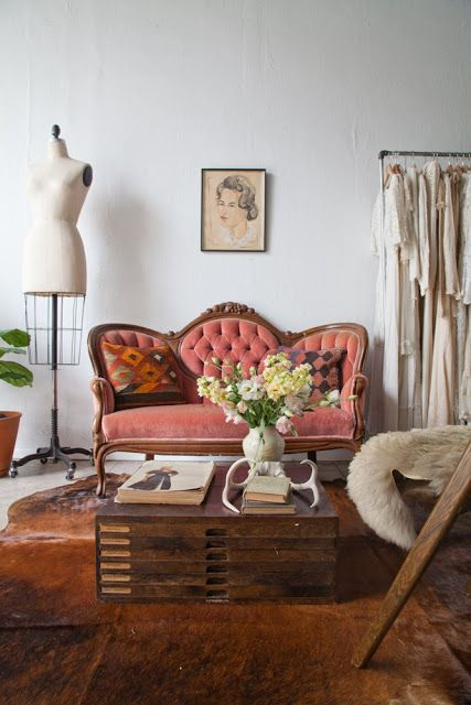 a sophisticated coral loveseat with wooden framing and tufted upholstery is a perfect match for this Parisian interior