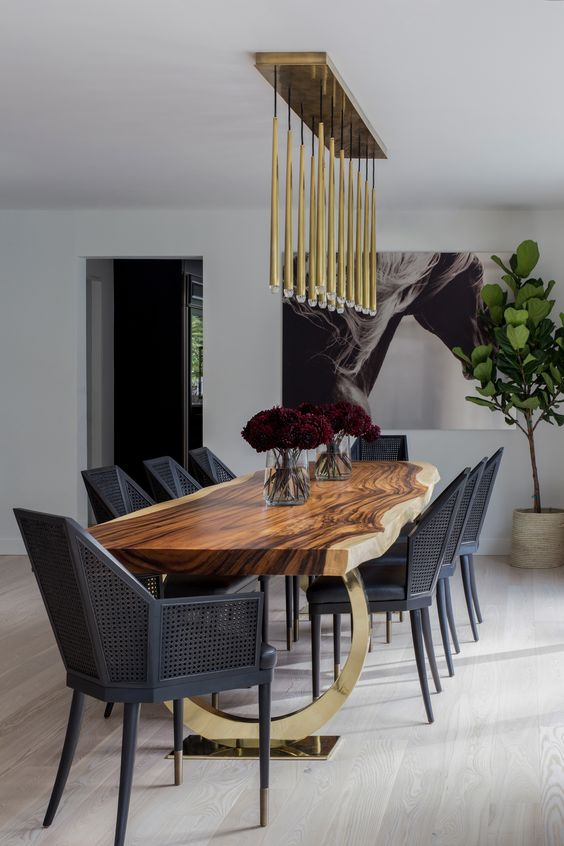 a super elegant and modern dining space with black geometric chairs, a live edge dining table and gilded touches