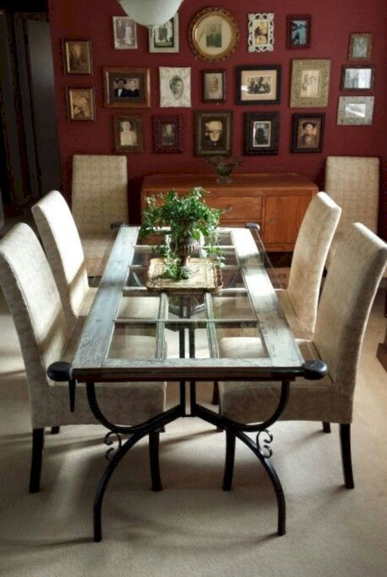 a vintage-inspired dining table featuring a vintage door, forged legs and a glass tabletop