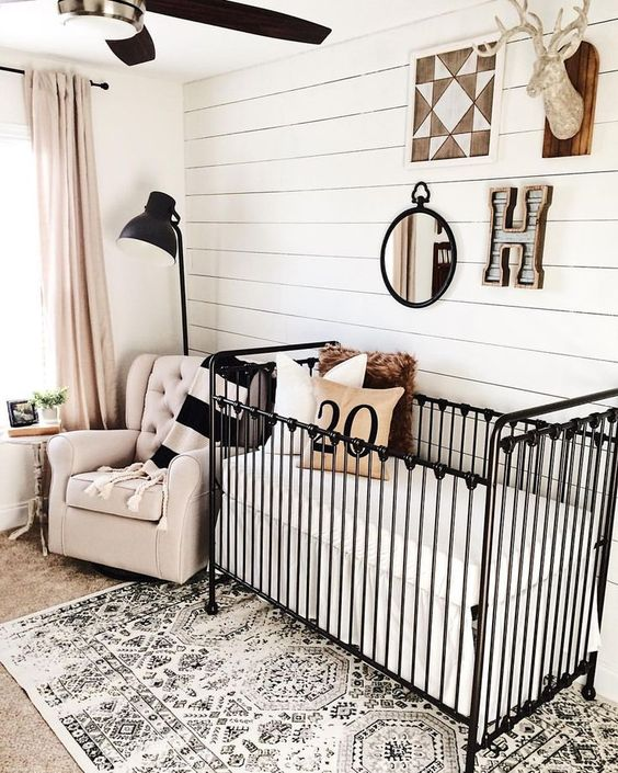 a farmhouse nursery with a woodland boho gallery wall, a printed rug and dramatic black touches