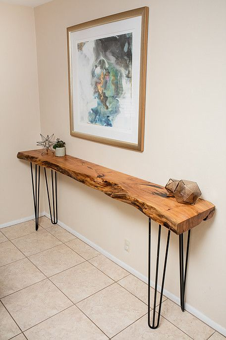 a very sleek and narrow entryway console table with a live edge and hairpin legs is a great way to fill in the space