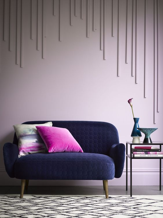a statement navy loveseat of textural velvet, bright pink pillows create a starck contrast and catch an eye