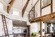 16 a white barndominium kitchen with wooden beams, pendant lamps, an oversized kitchen island