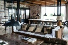 17 a moody industrial barndominium space with brick walls, dark stained wooden furniture and rough metal touches