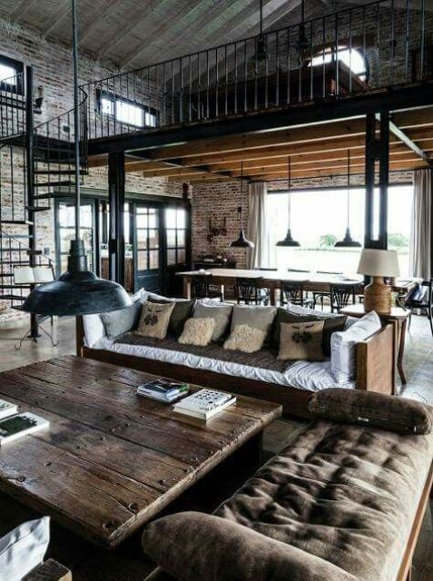 a moody industrial barndominium space with brick walls, dark stained wooden furniture and rough metal touches