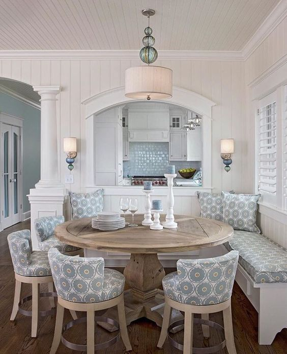 a rustic round table and patterned chairs and a bench for a cozy rustic dining space with a beachy feel