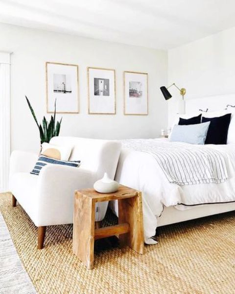 a stylish coastal bedroom finished off with a creamy loveseat on wooden legs for a cozier feel and comfortable sitting