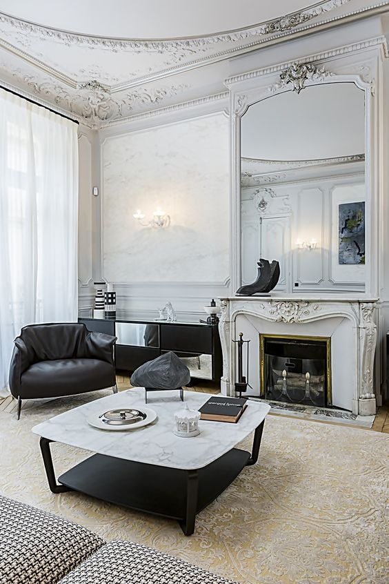 sophisticated molding on the walls, ceiling and fireplace make the contemporary black and white furniture more balanced