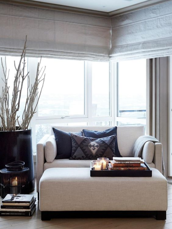 a stylish contemporary loveseat and a matching ottoman upholstered with neutral fabric to match the living room