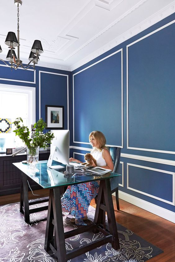 an elegant home office with navy and white walls, a dark blue patterned rug and a catchy trestle desk with a glass top