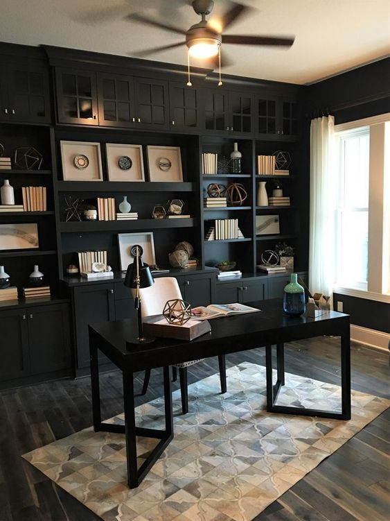 a black home office with a built-in wall unit and a polished desk is refreshed with some neutral touches