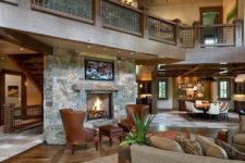 19 a cozy rustic barndominium space done with stone and wood, with warm-colored leather and a fireplace