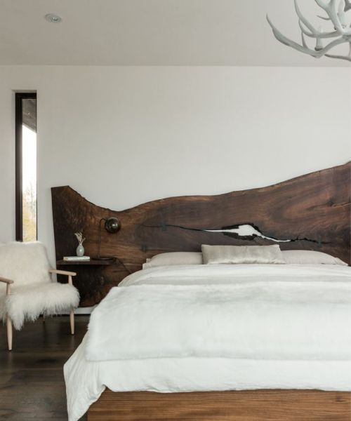 a modern bedroom with a rich stained live edge wooden headboard, an antler chandelier and a faux fur chair