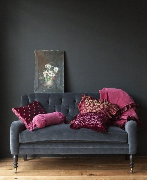 a super elegant black velvet loveseat with refined legs and fuchsia and purple pillows for a moody space