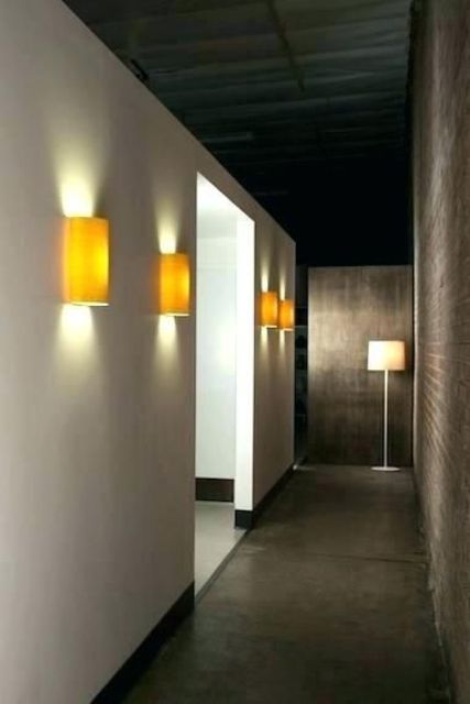 minimalist yellow wall sconces add color to the space and make the hallway lit up enough, though not too much