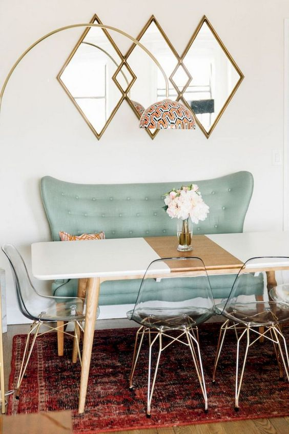 a catchy dining space with an aqua bench, clear acrylic chairs and a color block table