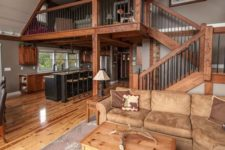 20 a cool rustic barndominium with much stained wood, light brown leather and traditional furniture