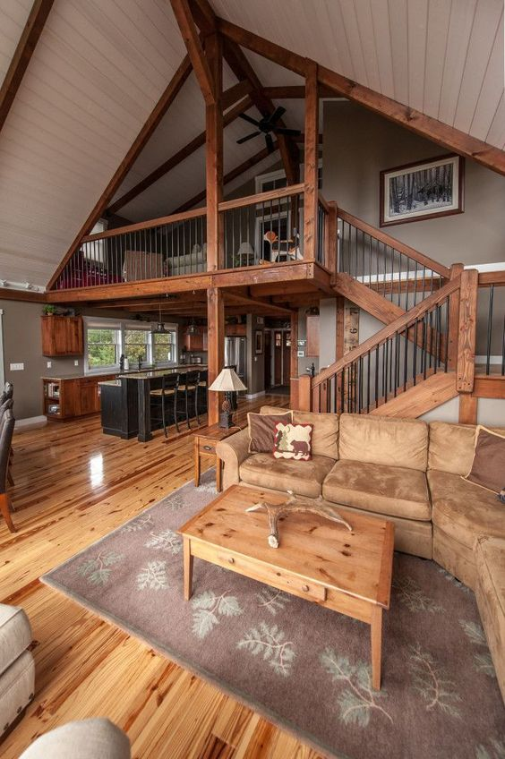 a cool rustic barndominium with much stained wood, light brown leather and traditional furniture
