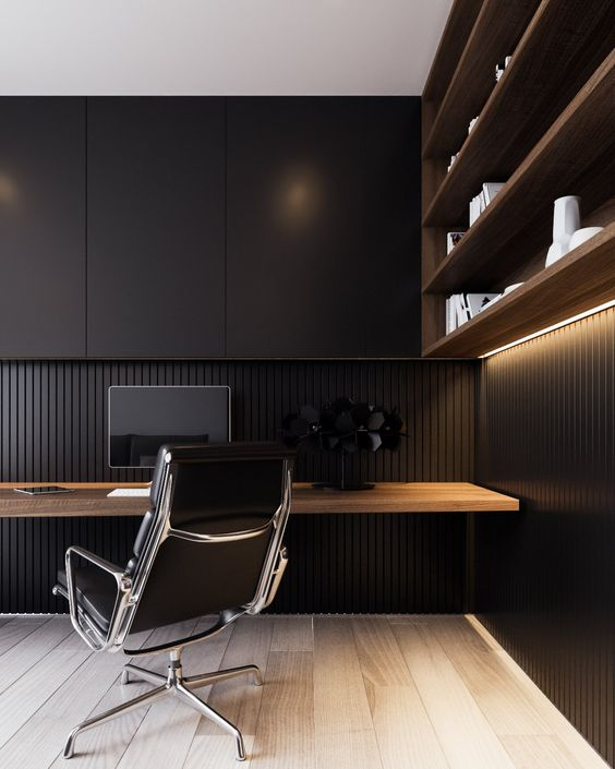 a minimalist black home office with a floating wooden desk and a shelving unit of rich stained wood