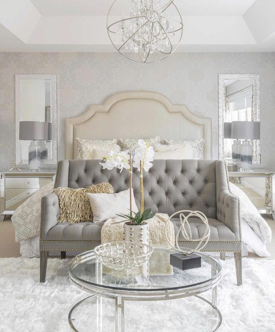 a super elegant grey tufted loveseat with a tall bench to create a sitting space at the bed