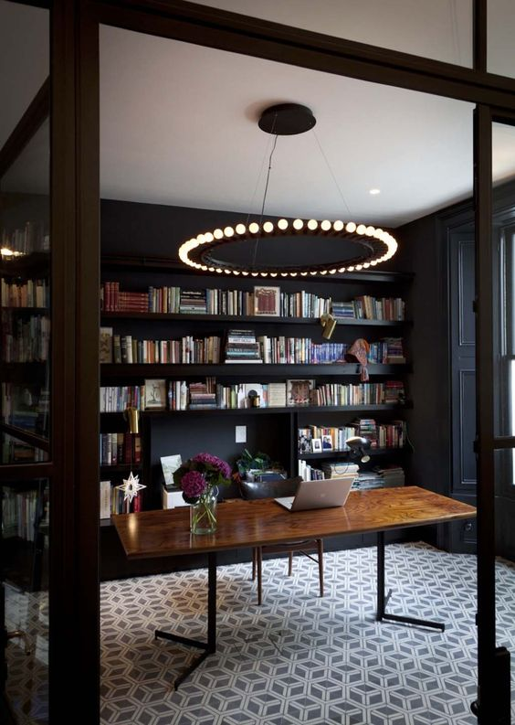 a black home office with bookshelves, a catchy modern chandelier, a wooden desk and a printed carpet