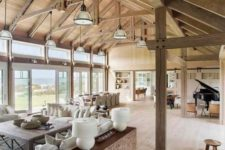 21 a contemporary meets rustic barndominium with glazed walls, pendant lamps, wooden and leather furniture