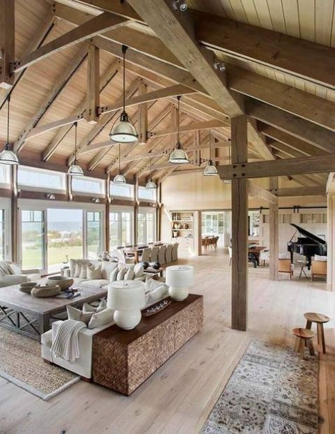 a contemporary meets rustic barndominium with glazed walls, pendant lamps, wooden and leather furniture