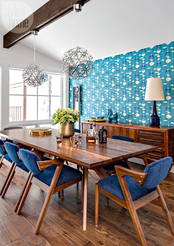a rich stained wooden dining table and matching rich wood and bright blue dining chairs that look bold