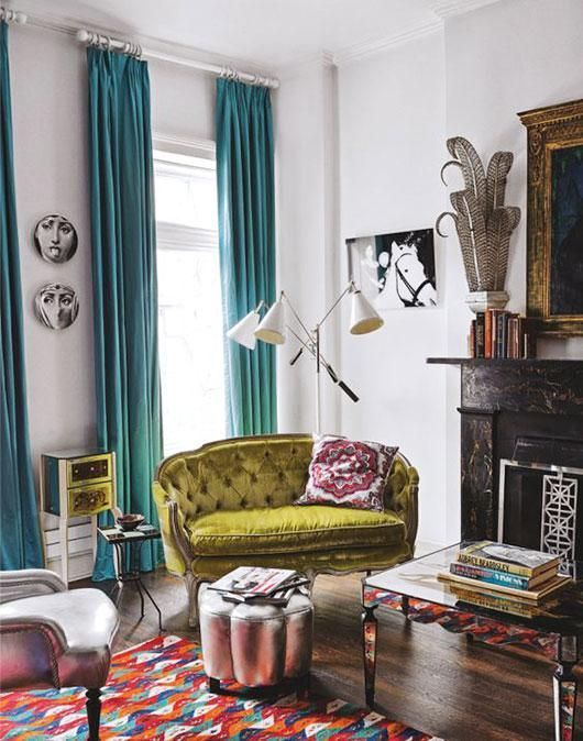 an eclectic living room with colorful touches and a pistachio green loveseat with tufted upholstery that adds chic