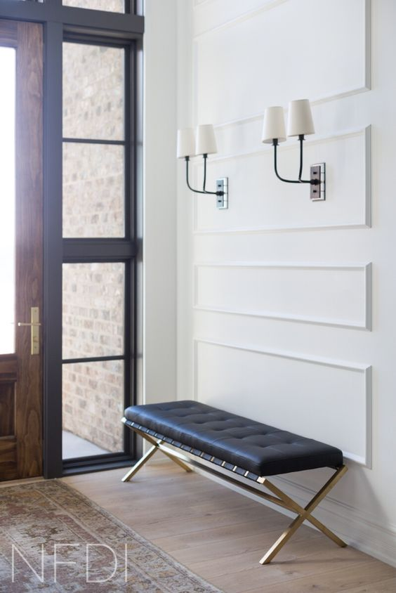black and white sconces match the black bench and make the hallway chic and bold