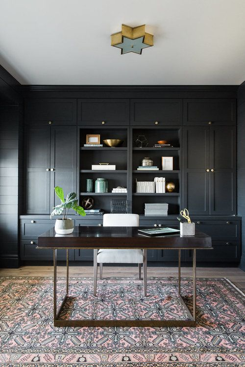 a retro-inspired home office in black with an oversized storage unit, a rich stained desk and a star lamp