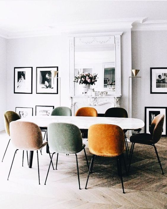 a white dining table and muted colored dining chairs for a light-filled Scandinavian dining space