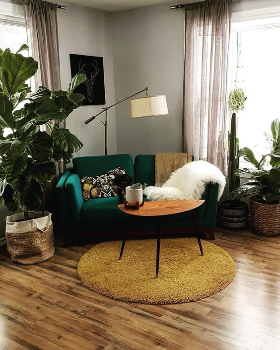 an emerald loveseat and a mustard rug create a chic mid-century modern nook in bright tones