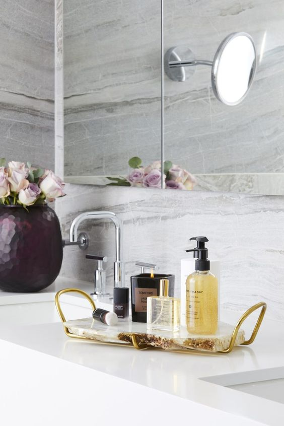 a chic and glam bathroom tray of agate and gold handles plus luxurious bath products