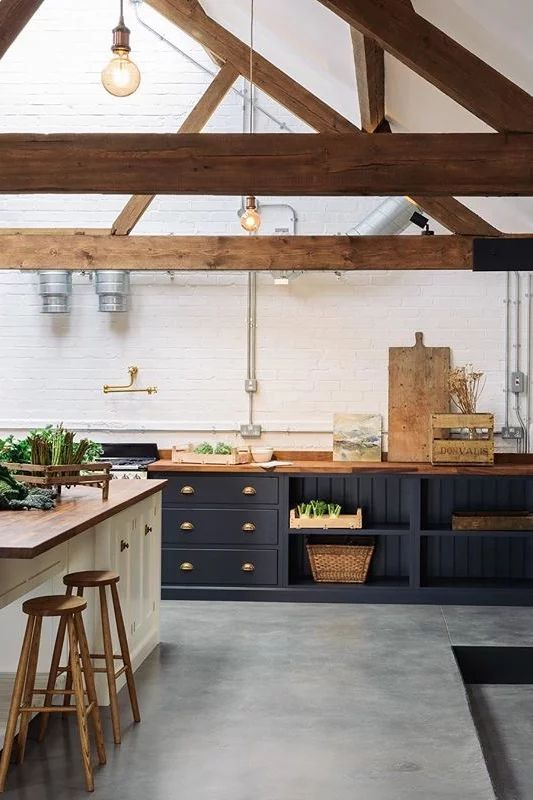 a chic barndominium kitchen with navy and white cabinets and wooden countertops and beams