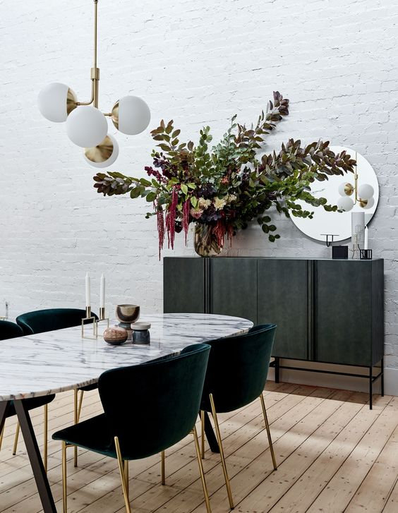 an oval dining table with a marble tabletop and dark green chairs with gold legs make the room very elegant