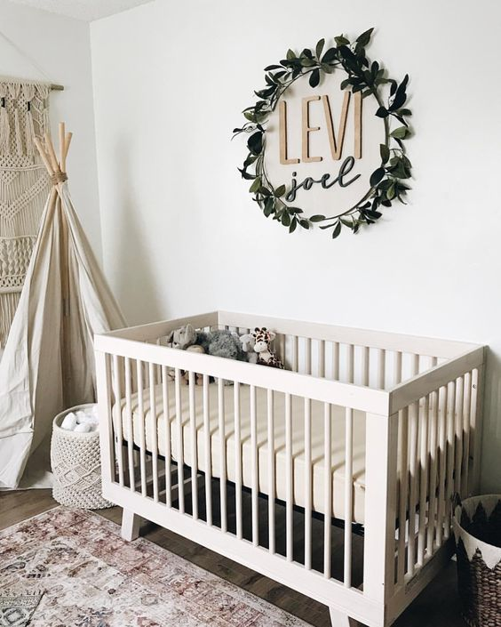 the name placed on the wall and accented with a fake greenery wreath is a stylish idea for a gender neutral nursery