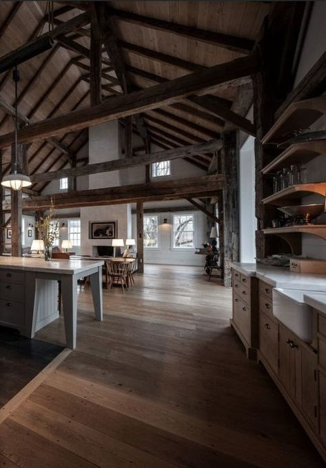 a cozy barndominium with multiple beams and much stained wood in decor, a white fireplace