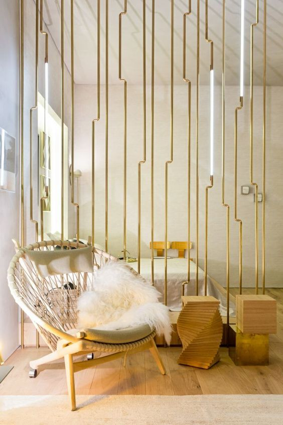 a minimalist room divider of wood and gilded metal plus lights looks really wow