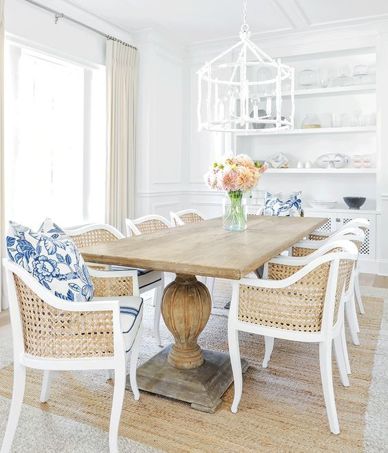 a rustic wooden table on large legs and cane chairs make up a traditional beach dining space
