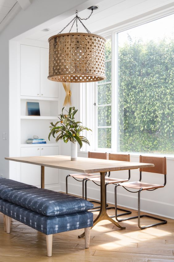 a sleek wooden dining table, wooden chairs and an upholstered blue bench for a mid-century modern space