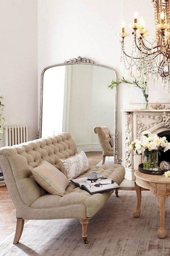 a super ornate fireplace and a crystal chandelier make this neutral space truly Parisian and tres chic