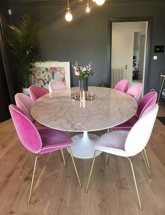 a glam dining space with a round marble dining table and white and pink velvet chairs