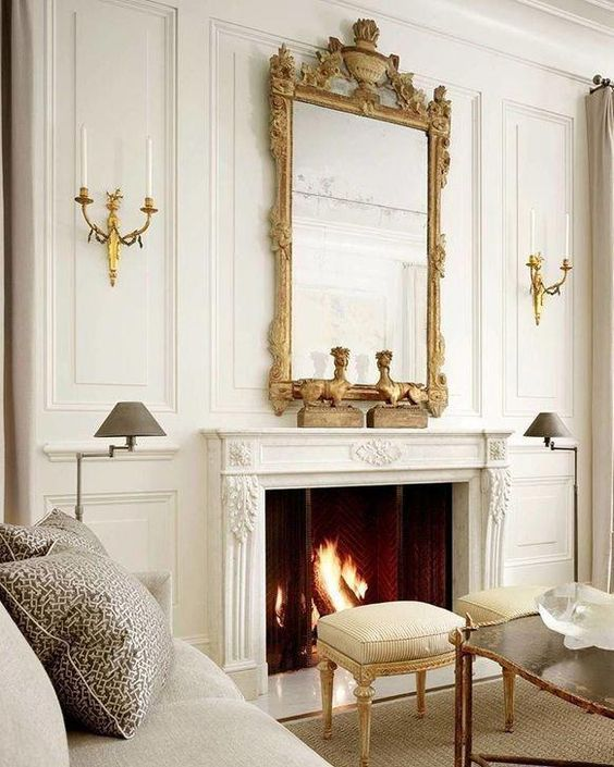 a neutral living room with a chic working fireplace that is accented with a vintage frame mirror that adds style