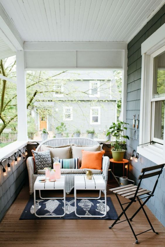 a white wicker loveseat can be easily squeezed into a small porch like this one to create a sitting space here