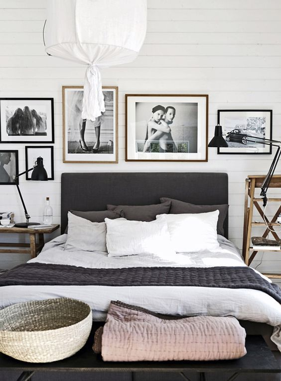 a Nordic black and white bedroom with a black bed, a gallery wall, mismatching wooden nightstands