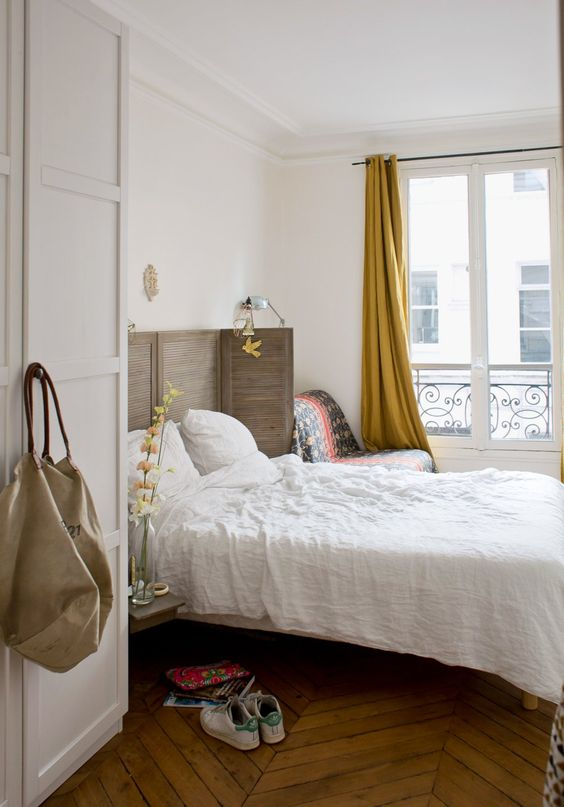 a Paris-inspired chic bedroom with a shutter screen as a headboard, a herringbone floor, mustard curtains and a comfy chair