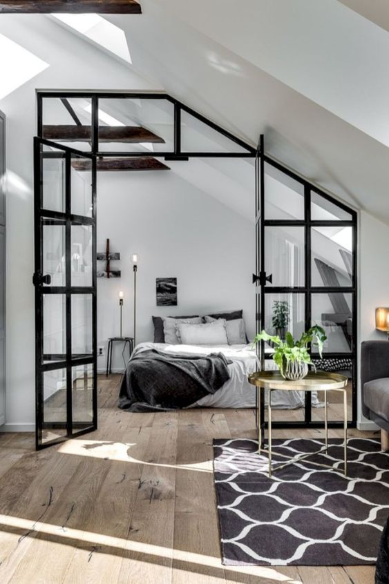 a Scandinavian bedroom in black and white, with a simple bed, floor lamps, dark wooden beams and a glass framed door