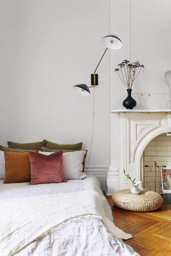 a beautiful Parisian bedroom with a faux fireplace, art deco lamps, a bed with muted pillows